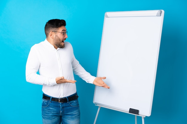 Businessman giving a presentation on white board giving a presentation on white board and with surprise expression
