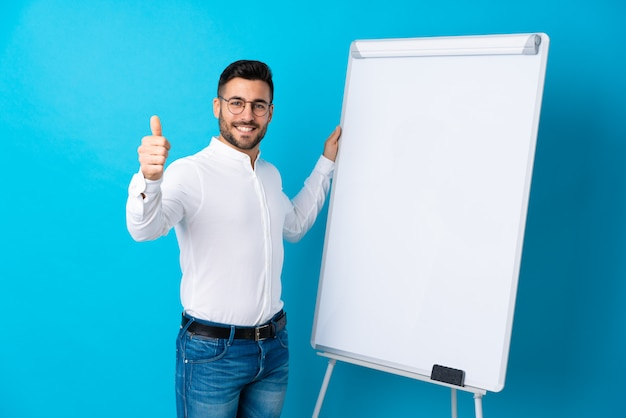 Businessman giving a presentation on white board giving a presentation on white board with thumb up