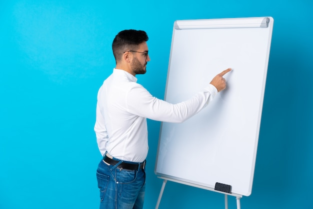 Businessman giving a presentation on white board giving a presentation on white board and writing in it
