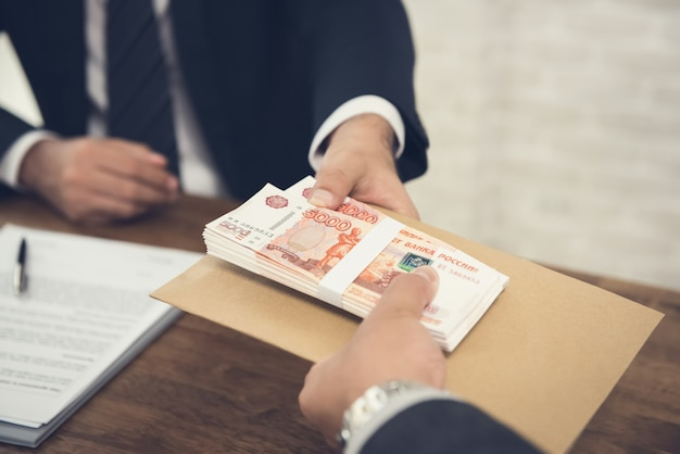 Businessman giving russian ruble to his partner