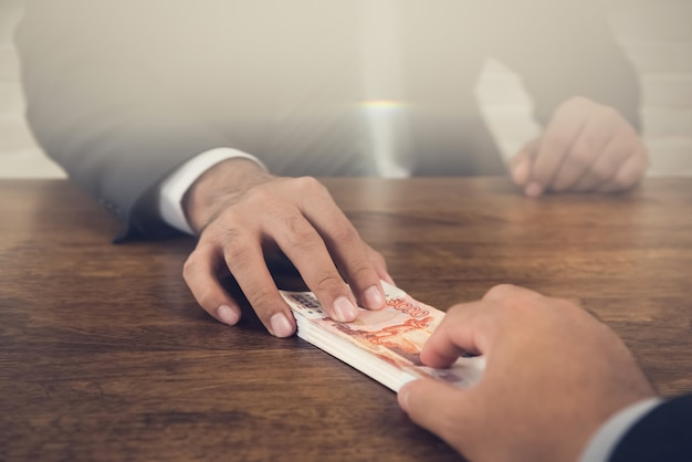 Businessman giving stack of money to his partner over an office desk