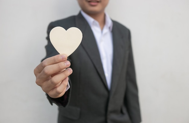 Businessman giving a white heart to a customer on white