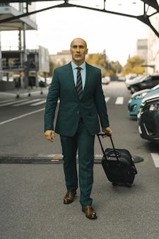 Бизнесмен идет вперед, держа в руке чемодан. красивый кавказский мужчина идет мимо припаркованного отеля