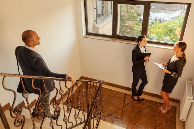 아래층으로 내려가는 사업가가 사무실 계단에서 동료를 만나고 있습니다. 기업 건물의 계단에 있는 비즈니스 임원 동료. 팀워크 파트너십. 바쁜 직장에서 전문적인 대화