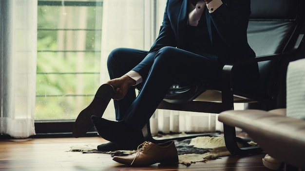 Businessman or groom tied a shoelace on his shoes.