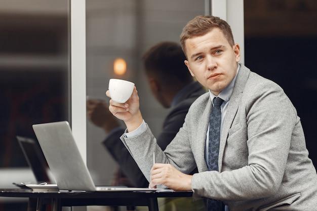 Бизнесмен. парень в костюме. мужчина пользуется ноутбуком.