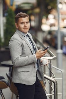 Бизнесмен. парень в костюме. мужчина пользуется мобильным телефоном.