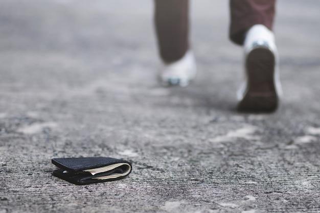 사업가는 길거리에서 돈이 든 가죽 지갑을 잃어 버렸다. 출근하는 동안 보도에 누워있는 지갑의 클로즈업.