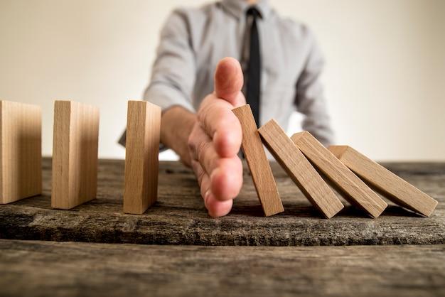 Businessman halting the domino effect