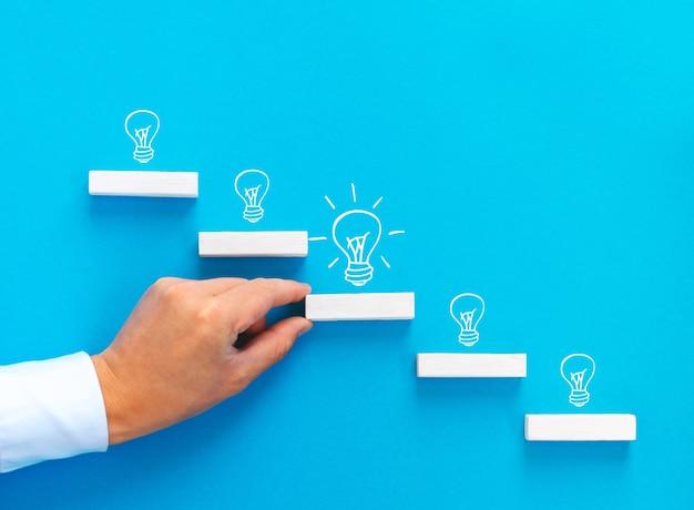 Рука бизнесмена укладка деревянных блоков как ступенчатая лестница с лампочкой. цели запуска бизнеса к успеху и концепция вдохновения идей с копией пространства.