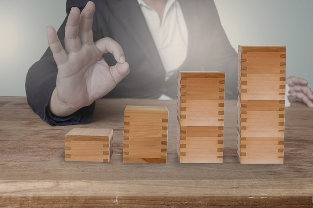 Businessman hand arranging wood cube stacking as step stair. business concept.