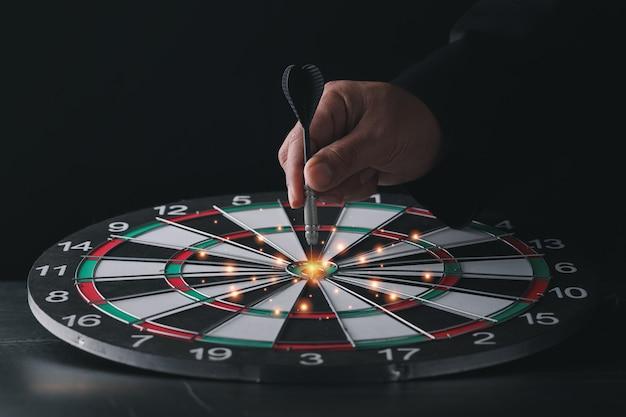 Businessman hand in black suite holding black dart put to center of target board on vintage table