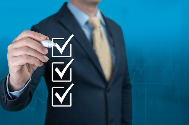 Businessman hand checking checklist boxes on blue background. businessman with pen mark check boxes