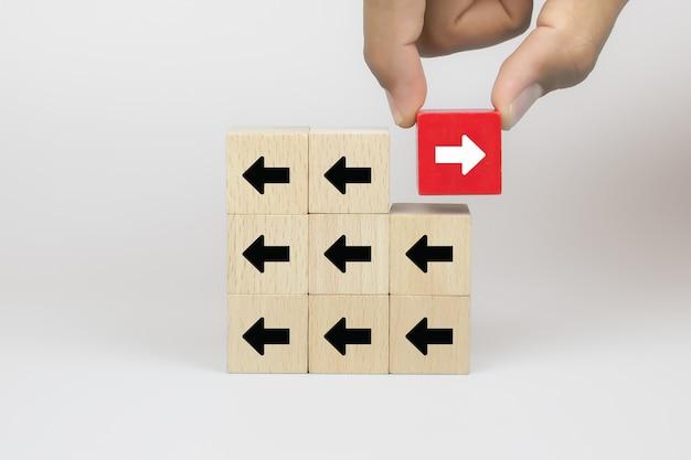 Рука бизнесмена выбирает блог деревянных игрушек куба со стрелками, указывающими на противоположные направления для изменения бизнеса