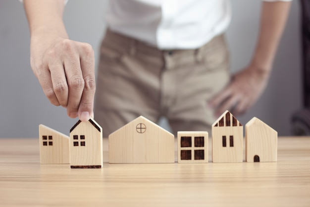 Businessman hand choosing house wood model and planning to buy property