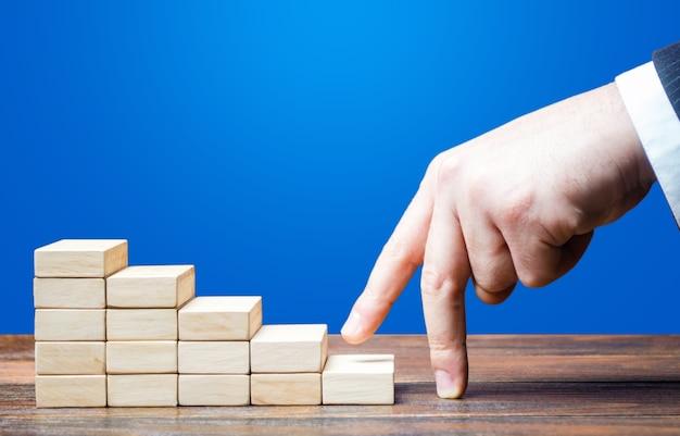 Businessman hand climbs career ladder of success.