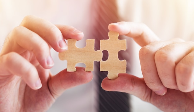 ジグソーパズルを接続するビジネスマンの手。ビジネスソリューション、成功と戦略の概念。