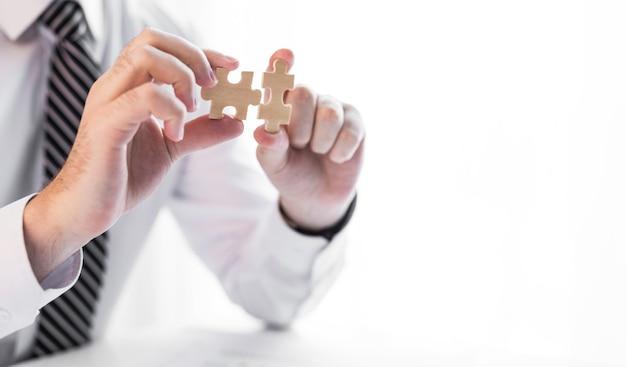 지 그 소 퍼즐을 연결하는 사업가 손. 비즈니스 솔루션, 성공 및 전략 개념입니다.