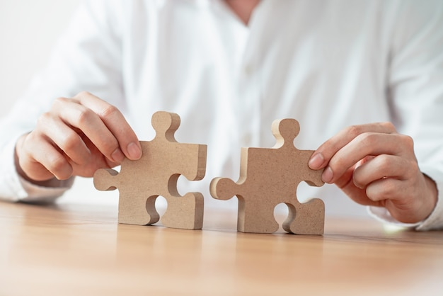 Businessman hand connecting jigsaw puzzle on desk.