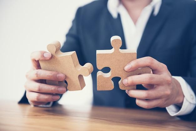 机の上のジグソーパズルを接続するビジネスマンの手。
