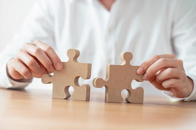 Бизнесмен рука подключения головоломки на столе.