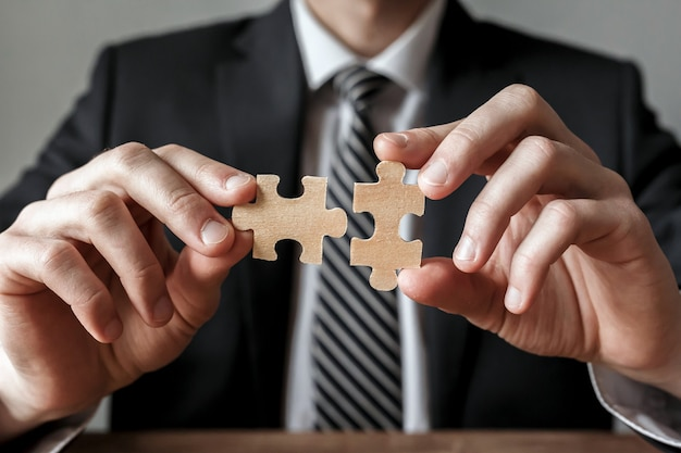 Businessman hand connecting jigsaw puzzle