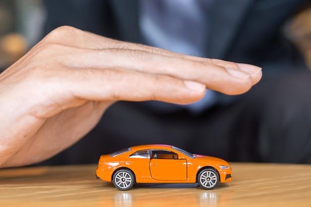 사업가 손 덮개 또는 테이블에 보호 오렌지 자동차 장난감