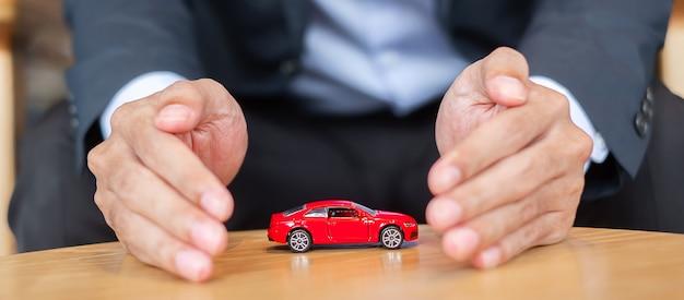 사업가 손 덮개 또는 테이블에 보호 빨간 자동차 장난감