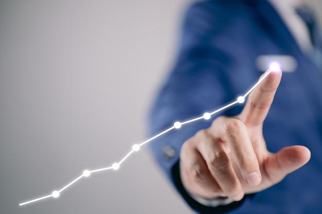 ビジネスマンの手は、タッチスクリーンでビジネスグラフを描きます