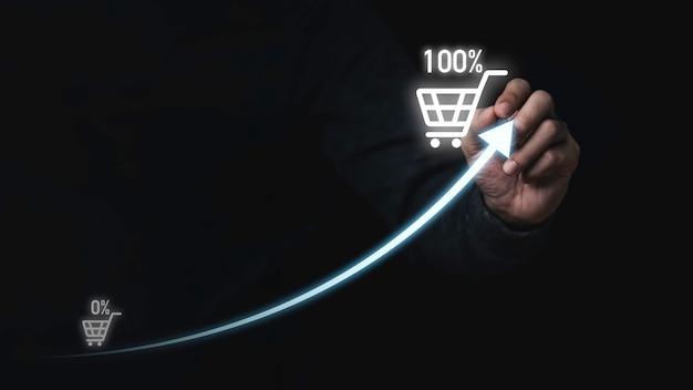 販売ビジネスとショッピングの成長の概念のための増加する矢印とショッピングトロリーカートを描くビジネスマンの手描き。