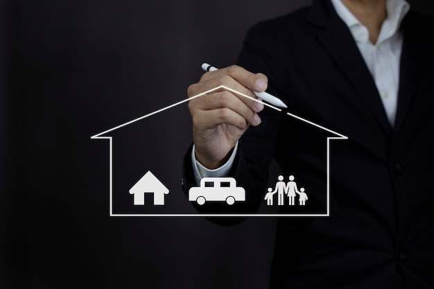 Businessman hand drawing protective home car family icon