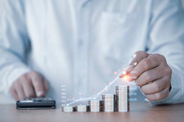 Рука бизнесмена рисуя виртуальный увеличивающийся график с укладкой денежных монет, прибылью от инвестиций в бизнес и экономией дивидендов по депозиту в концепции 2021 года.