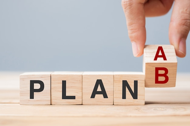 Businessman hand flipping wooden cube blocks with plan a change to plan b text on table background. strategy, leadership, management, marketing, project and crisis concepts
