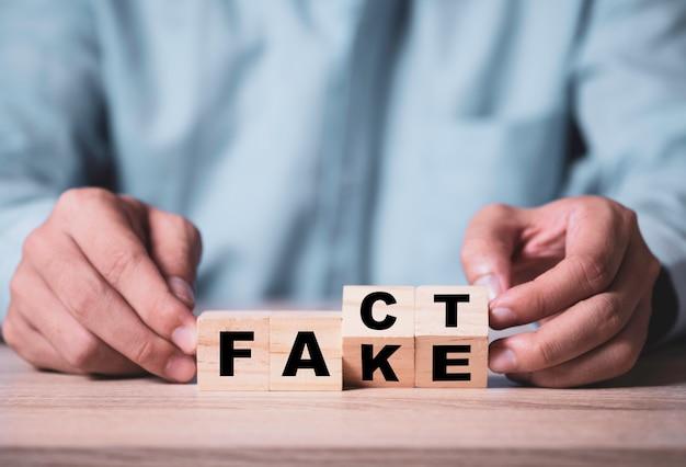 実業家の手が「偽」から「事実」への言い回しを変更するための木製キューブをめくる
