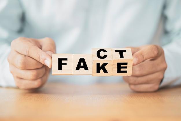 「偽物」から「事実」への言い回しを変更するために、ビジネスマンが木製の立方体を手でひっくり返します。