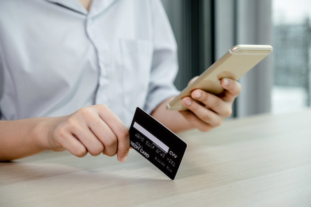 Businessman hand hold credit card to online shopping on smartphone from home, payment e-commerce, internet banking, spending money for next holidays.