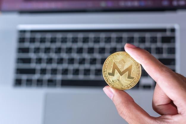 Рука бизнесмена удерживает золотую монету криптовалюты monero (xmr) над клавиатурой ноутбука, монета monero. крипто - это цифровые деньги в сети блокчейнов.