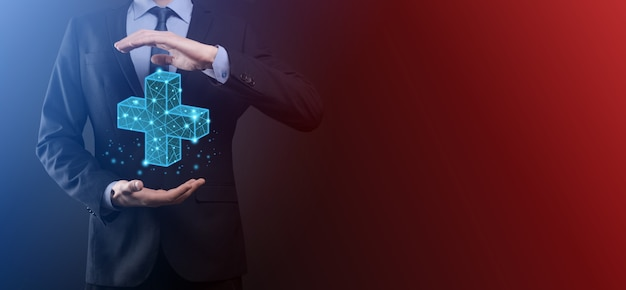 3dと低い多角形のアイコンを持っているビジネスマンの手。プラス記号仮想手段は、利益、自己啓発、ソーシャルネットワークの利益、健康保険、成長の概念などの肯定的なものを提供します。