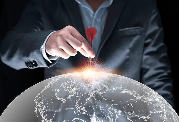 실업가 손을 잡고 검은 배경 및 세계지도에 보드를 대상으로 빨간 다트를 trowing. 비즈니스 및 투자 대상 개념입니다.