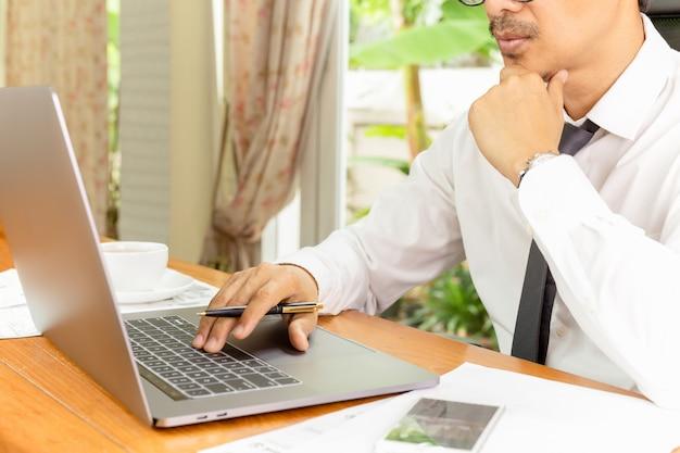 Businessman hand holding ballpoint pen working on laptop computer