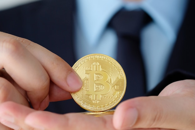 Businessman hand holding bitcoin, close up, finance, cryptocurrency and blockchain concept