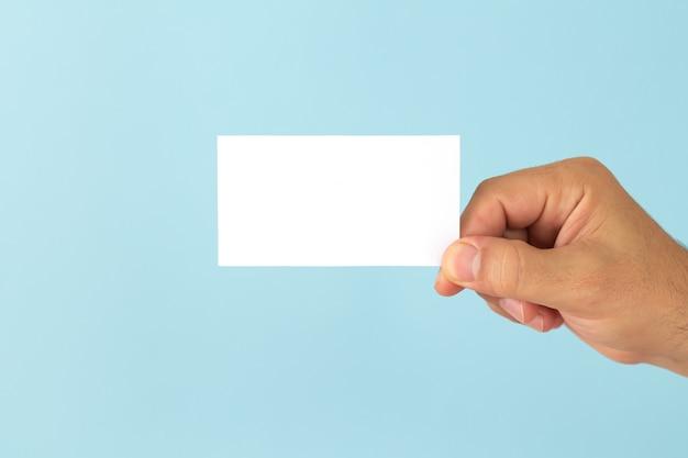 Рука бизнесмена держа пустую визитную карточку на голубом фоне.