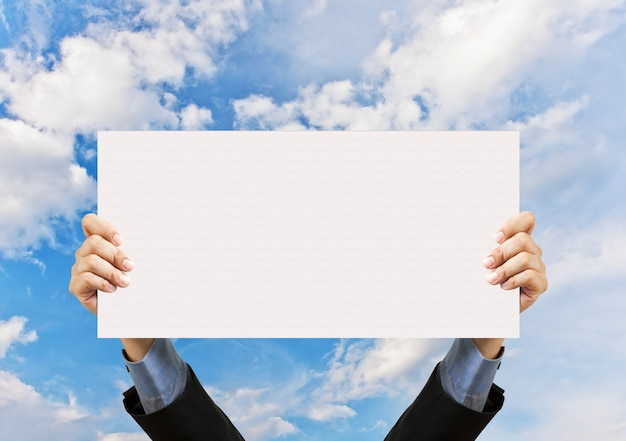 Businessman hand holding blank sign and blue sky