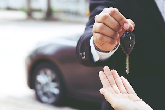 新しい車で車のキーフロントを持っているビジネスマンの手。輸送の概念。
