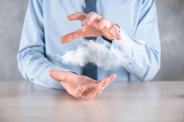 クラウドを持っているビジネスマンの手。クラウドコンピューティングの概念、彼の手の上にクラウドを持つ若いビジネスマンのクローズアップ。