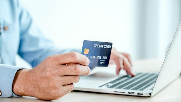Бизнесмен рука кредитной карты для покупок в интернете из дома.