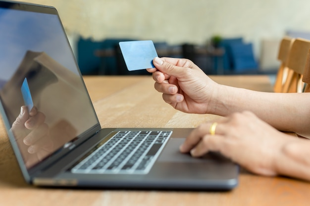 Businessman hand holding credit card and using laptop on wooden table.