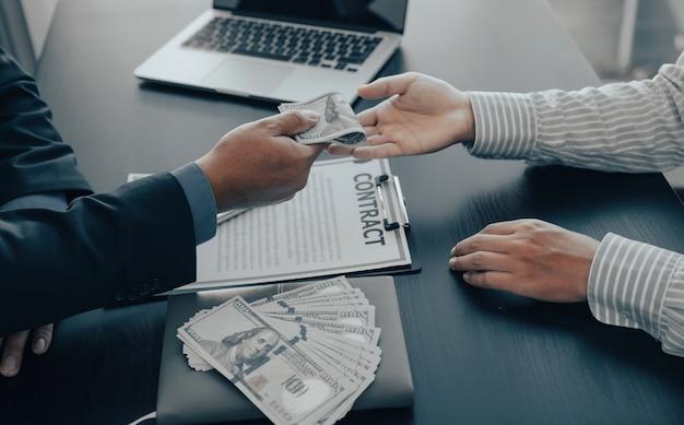 Рука бизнесмена, держащая деньги банкноты доллара, чтобы подкупить финансовых чиновников или босса, выплачивает зарплату персоналу и противодействует взяточничеству.