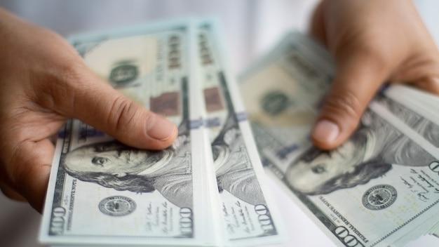 투자 수익에서 성장 이익을 분석하는 달러 지폐를 들고 사업가 손