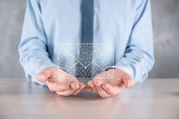 電子メールアイコンを持っているビジネスマンの手、ニュースレターの電子メールで私達に連絡し、スパムメールからあなたの個人情報を保護します。概念。